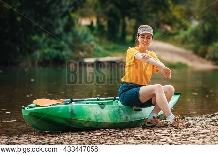 Dissatisfied Woman Is Sitting On A Kayak And Scratching Her Hand From A Mosquito Or Flea Bite. The C