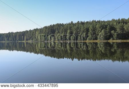 Summer Serene Landscape With Green Woods, Its Reflection In River Water, Clear Blue Sky Horizon.