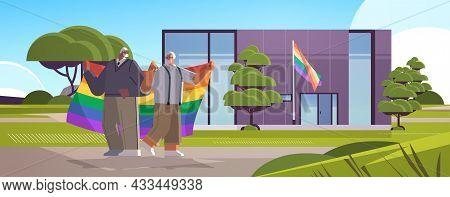 Senior Gay Couple Holding Rainbow Flag Near New Modular House Transgender Love Lgbt Community Concep