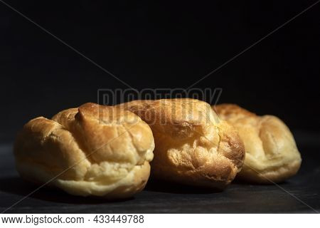 Profiteroles, Puffs, Popovers, Eclaires On Black Background Close Up