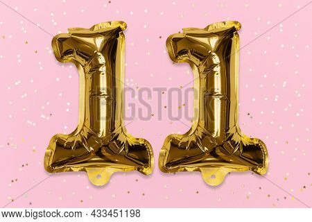 The Number Of The Balloon Made Of Golden Foil, The Number Eleven On A Pink Background With Sequins.