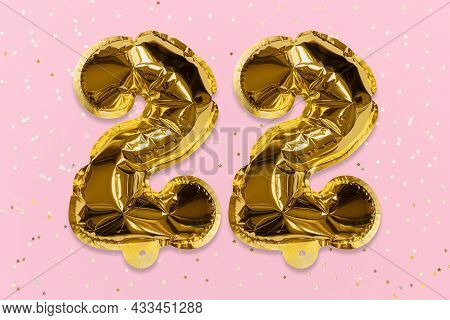 The Number Of The Balloon Made Of Golden Foil, The Number Twenty Two On A Pink Background With Sequi