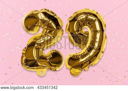 The Number Of The Balloon Made Of Golden Foil, The Number Twenty-nine On A Pink Background With Sequ