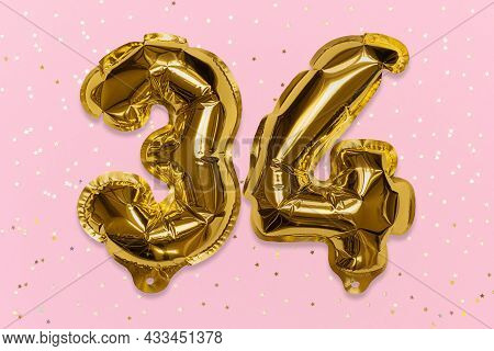 The Number Of The Balloon Made Of Golden Foil, The Number Thirty-four On A Pink Background With Sequ