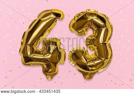 The Number Of The Balloon Made Of Golden Foil, The Number Forty Three On A Pink Background With Sequ