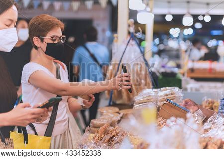 Woman Customer In Protective Mask Hand Showing Online Payment In Cell Phone During Covid-19