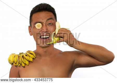 Portrait of funny young man with banana pince-nez and epaulette telephoning with banana isolated on white background