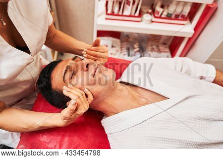 Masseuse Pulling Skin Of Male Cheeks Up With Hands