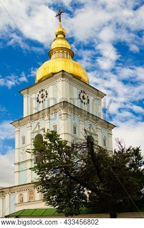 Close-up View Of High Bell-tower With Clock And Golden Dome. Fantastic Soft Clouds In The Background