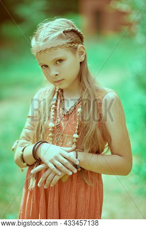 Portrait of a cute girl child dressed in hippie style on a blurred summer background. Kid's fashion.