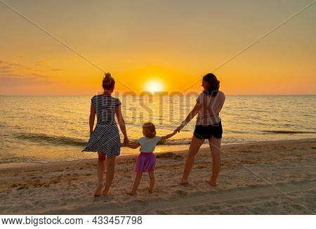 Two Young Women Hold Hands A Little Girl, Standing On The Sea Beach On A Summer Evening. In The Back