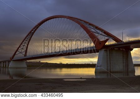 The Arch Of The Bugrinsky Highway Bridge Across The Ob River In Novosibirsk. Yellow-blue Sky At Dawn