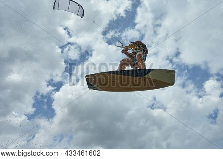 Kitesurfer in the cloudy sky with a kiteboard
