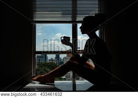 Silhouette young woman drinks coffee in morning at window