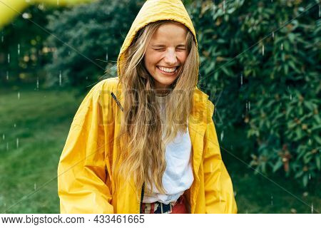 Playful Young Blonde Woman Smiling Wearing Yellow Raincoat During The Rain In The Park. Cheerful Fem