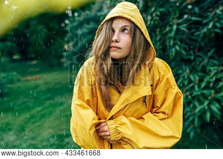 Sad Young Blonde Woman Looking Up, Wearing Yellow Raincoat During The Rain In The Park. The Unhappy