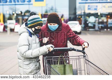 Old Senior Woman And Kid Boy With Medical Mask Due Pandemic Coronavirus Disease. Child Help Grandmot