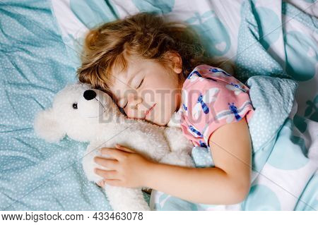 Cute Little Toddler Girl Sleeping In Bed With Favourite Soft Plush Toy Teddy Bear. Adorable Baby Chi