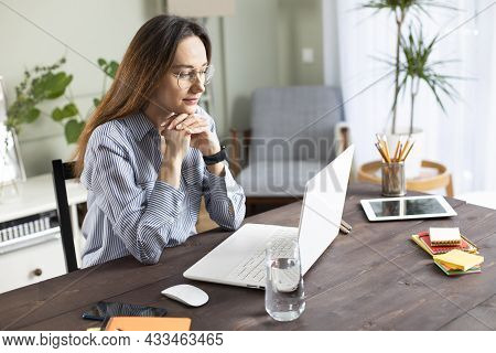 Young Woman Working With A Laptop. Female Freelancer Connecting To Internet At Home. Blogger Writing