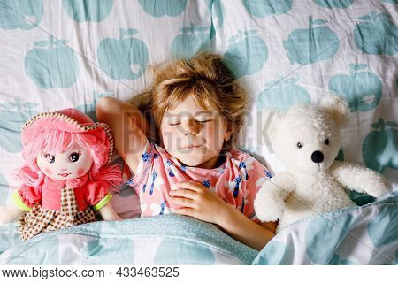 Cute Little Toddler Girl Sleeping In Bed With Favourite Soft Plush Toy Doll And Teddy Bear. Adorable