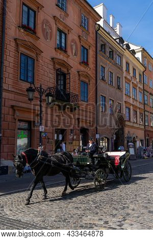 Black Horse And Carriage On A Cobblestone Street In The Historic Old Town Of Warsaw