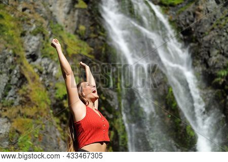 Excited Woman In Red Raising Arms In A Waterfall Celebrating Holiday