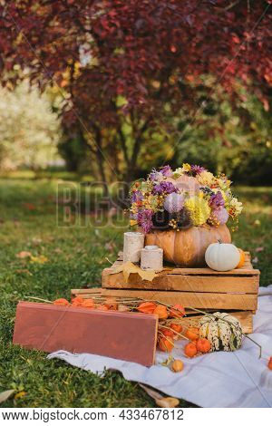 Autumn Bouquet Of Beautiful Flowers And Berries In A Pumpkin On Wood In The Garden. Concept Of Autum