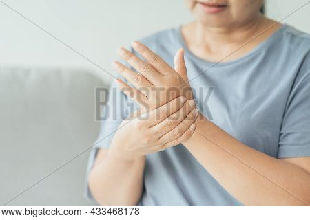 Closeup Of Woman Sitting On Sofa Holds Her Wrist. Hand Injury, Feeling Pain. Health Care And Medical