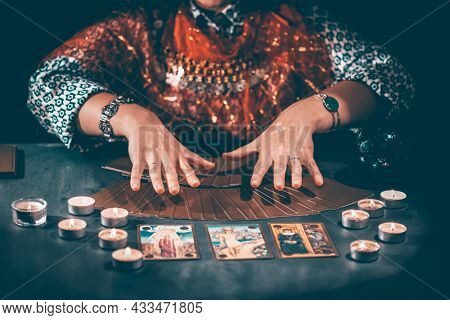 Fortune teller with tarot cards on table near burning candles.Tarot cards spread on table with crystal ball.Forecasting concept.
