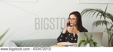 Beautiful Woman Sits In A Cafe, Drinks Coffee, Works On A Computer And Uses A Phone