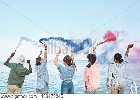 Five ecstatic intercultural friends with colorful firecrackers having fun by waterside