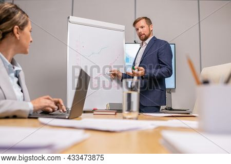 Contemporary coach pointing at whiteboard at seminar while looking at businesswoman with laptop