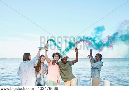 Cheerful intercultural young friends with firecrackers dancing by waterside on summer day