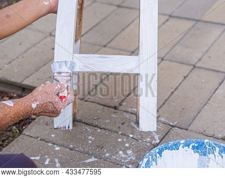 Senior Man Holding Brush For Paint White On Old Wooden Chair Without A Backrest Hand Of Man. Old Cha