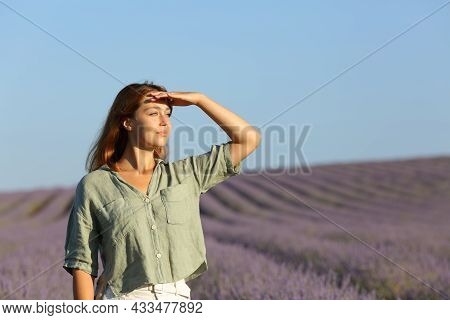 Happy Woman Contemplating Lavender Field Protecting From Sun With Her Hand