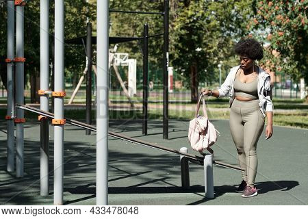 Young plus size female in sportswear putting handbag on facilities before outdoor training