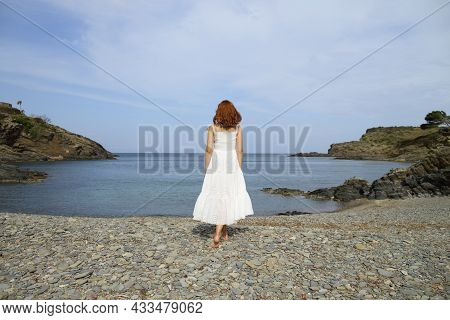 Back View Full Body Portrait Of A Woman Walking Towards Water Contemplating Views On The Beach