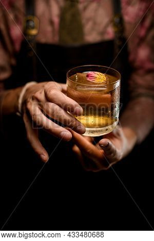 Hands Of Man Accurate Holds Glass Of Cocktail Decorating With Beautiful Flower Petal