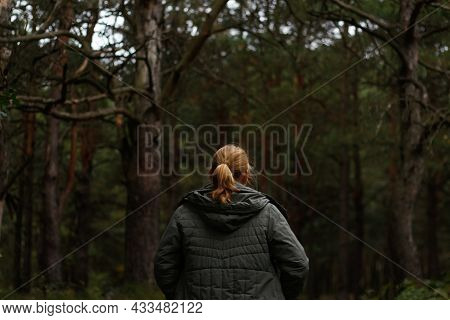 Defocus Back View Of A Young Blonde Woman Hiking In Forest. Hiking Woman Walking In Gloomy Mystical