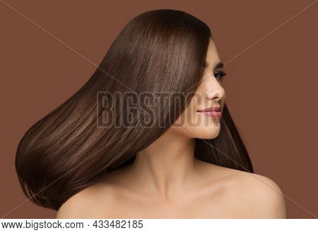 Hair Beauty Model. Brunette Woman With Long Straight Shiny Hairstyle Over Dark Beige Background. Hea