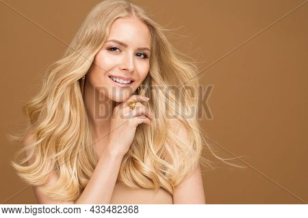 Happy Smiling Beauty Woman With Blond Curly Hairstyle. Model Gil Face With Natural Make Up Over Beig