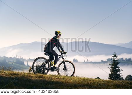 Side View Of Cyclist In Cycling Suit Riding Bicycle On Grassy Hill And Looking At Beautiful Misty Mo