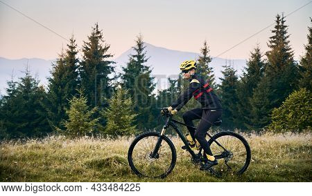 Side View Of Cyclist In Cycling Suit Riding Bike With Coniferous Trees And Hills On Background. Man