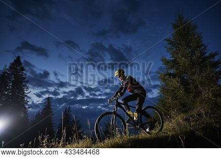 Man Cyclist Riding Bicycle Downhill With Beautiful Blue Evening Sky On Background. Male Bicyclist In