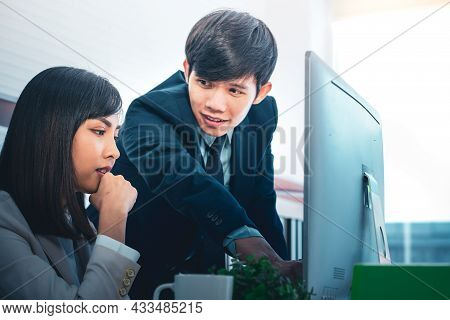 Young Asian Man Looking At Coworker And Discussing And Advising Something At Office.