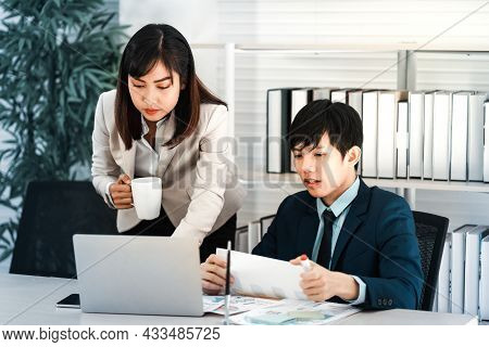 At Work, A Young Attractive Woman Is Gazing At Her Computer And Conversing With A Coworker. At Work,