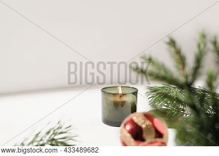 Green Scented Christmas Candle Next To Pine Branch And Red Christmas Ball. Copy Space. Holiday Home