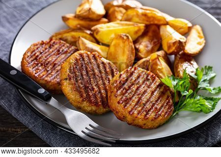 Grilled Fish Burgers With Baked Potato Wedges On A Plate, Close-up