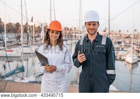 Positive Competent Professional Male And Female Port Employees In Hardhats And Protective Uniform Wi