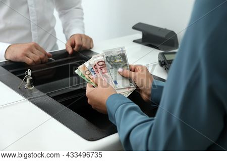 Woman With Money At Currency Department Window In Bank, Closeup